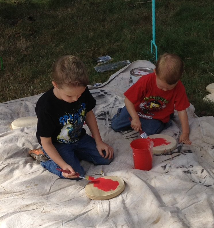 Gage (age 4) and Ryker (age 2) Mead of Clifford busily paint the human-sized checkerboard for the Clifford Children's Garden.