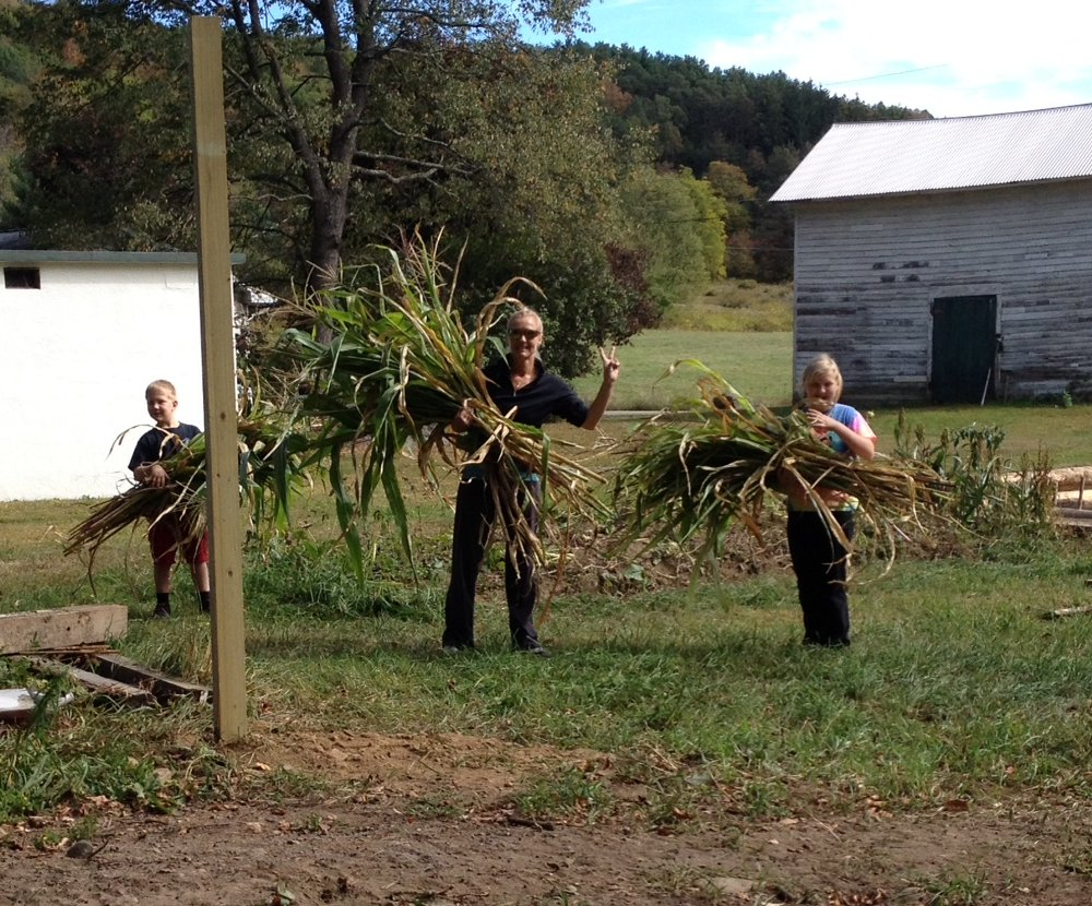 Conrad, Christine, and Ava Depew of Clifford have fun gathering cornstalks to sell as a fundraiser for the Clifford Children's Garden.